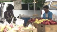 general views of consumers paying for produce at farm stands / union square farmers market Consumers at Farmers Market on May 23 2012 in New York New...