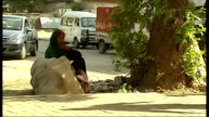 General views of daytoday life in Islamabad Rawalpindi and the Afghan border area PAKISTAN Islamabad EXT Homeless woman seated as stands and hoists...
