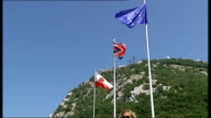 EXT Union Jack flag flying / skyline with sea in background / tourists taking photographs / Union Jack European Union and Gibraltar flags flying /...
