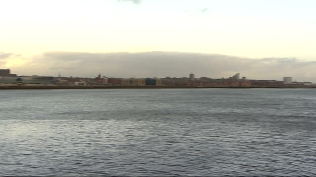 River Mersey skyline / railway station / derelict buildings / residential tracking shots Ships moored at docks and buildings seen across River Mersey...