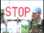 UN security checkpoint UN soldier searching car at checkpoint / soldier turning 'Go' sign to 'Stop' sign / troops at checkpoint / mural of Liberian...