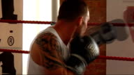 General views of people training inside The Real Fight Club gym Various of men shadow boxing in gym Various of man throwing punches in ring against...