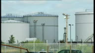 General views of Stanlow Oil Refinery ENGLAND Cheshire Stanlow Oil Refinery EXT Pipes over road / Cars along past refinery tanks / More of pipes /...