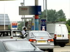 General views of Tesco and Asda petrol stations ENGLAND EXT Motorist filling his car with fuel at Tesco petrol station / general view of cars queuing...