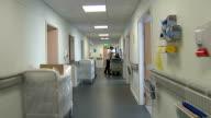 General views of Watford General Hospital and Callowland doctor's surgery Medical staff along in corridor / hospital ward / TRACKING SHOT along...