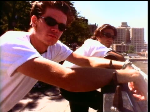 2 Generation X men in sunglasses leaning on railing turn + look at camera outdoors