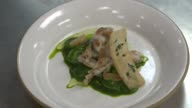 Generic footage of cooking in a restaurant's kitchen as dishes are prepared in Brooklyn NY on July 27 2017 Shots CU of ravioli with green sauce being...
