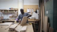 Generic machine making eyeglasses workers processing wood and painting footage the Brooklyn Army Terminal in Brooklyn NY on August 8 2017 Shots full...