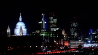 Generic shots of commuters and the City of London by night Canary Wharf skyline with illuminated Blackfriars Bridge in foreground PAN to city skyline...