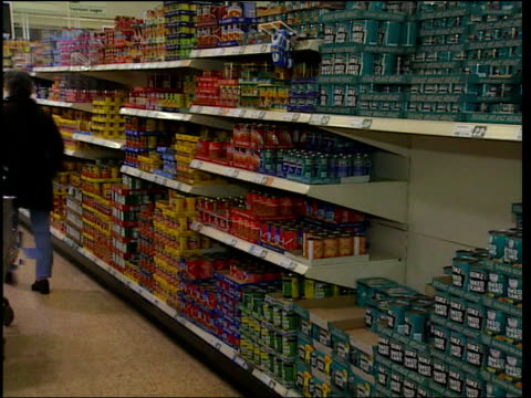 Labelling/Pollen LIB Asda supermarket LBV woman taking tin of baked beans off shelf and along down aisle BV woman taking tin of Heinz baked beans off...