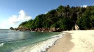 Gentle waves lap onto a sandy beach on Cousine Island, Seychelles.