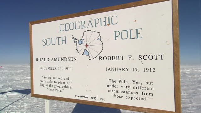 PAN Geographic South Pole sign next to waving American flag / Antarctica
