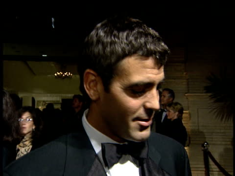 George Clooney talks to reporter about why stars support the ball and what he's wearing after greeting man on red carpet