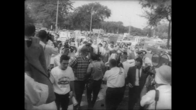 George Lincoln Rockwell leader of American Nazi Party walks along talking surrounded by crowd of press /crowd carrying signs reading 'WHITE POWER' /...