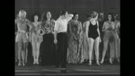 George White writer producer and director of show 'Scandals' walks onto stage past chorus girls sitting and waiting he commands them to stand up and...
