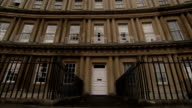 A Georgian terrace leads to the white door of a townhouse in The Circus in Bath, England. Available in HD.