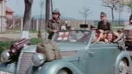 German Army soldiers in convertible with Red Cross sign and trucks driving past US Army MP to surrender