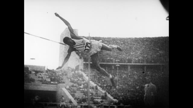 / German athlete performs high jump but fails / Japanese athlete fails / African American athlete Cornelius Johnson jumps and makes it / crowd goes...