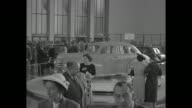 German attendees amble through auto exhibit with an Opel Kapitan sedan car on a turntable
