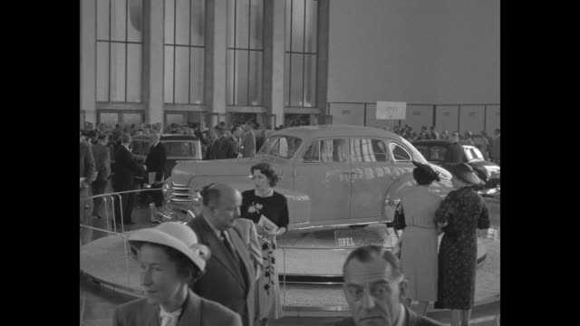 German attendees amble through auto exhibit with an Opel Kapitan sedan car on a turntable