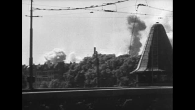 German bombers flying over city dropping bombs tilt down to bombs exploding pan across bombs exploding to ship burning at dock in harbor / bombers...