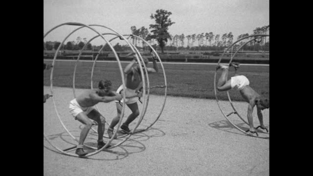 German boys and girls riding inside round steel hoops on racetrack / young men exercise in hoops moving them back and forth / two girls get into hoop...