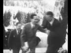 German Chancellor Adolf Hitler kneels smiles as he talks with little boy at his Berchtesgaden estate woman stands in background / Berlin district...