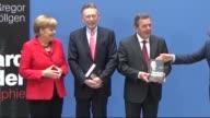 German Chancellor Angela Merkel and former German Chancellor Gerhard Schroder attend author Gregor Schollgen's book launch in Berlin Germany on...