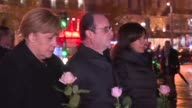 German Chancellor Angela Merkel and President Francois Hollande each lay pink rose on the growing pile of tributes in Place de la Republique the...