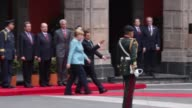 German Chancellor Angela Merkel walks accompanied by Mexican President Enrique Pena Nieto during a reception as part of an official visit of German...