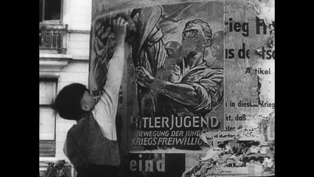 / German children burning Nazi symbols / young boy scrubbing Nazi poster off the wall Children Destroy Nazi Symbols in Post War Germany on January 01...