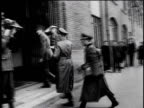 German military officials getting out of car under armed guard / WS German officers walk into building / WS Military officials seated at conference...
