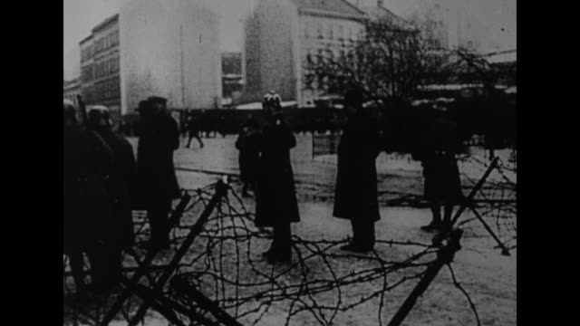 German military personnel stand outside on snowy street barbed wire stands in foreground / German newspaper headline calls for reforming the Nazi...