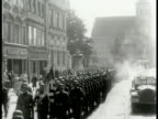 POLAND German Nazi soldiers marching down street Polish people standing by side of street watching soldiers passing FG HA German Nazi soldiers...