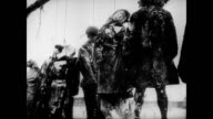 / German officer standing in front of a makeshift gallows / dead people hanging from their necks in a line / CU of the bodies hanging German...