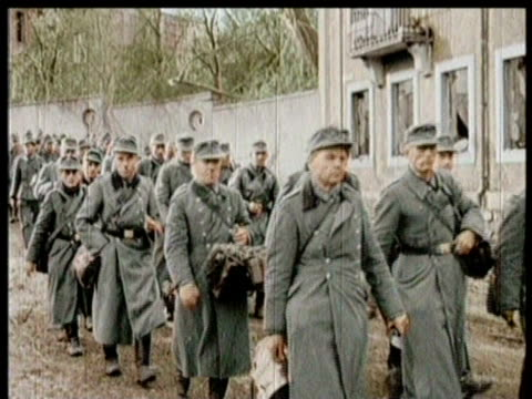 German soldiers are marched through the town / a man resolutely smokes a pipe / one soldier carries a white flag of surrender / they are lined up in...