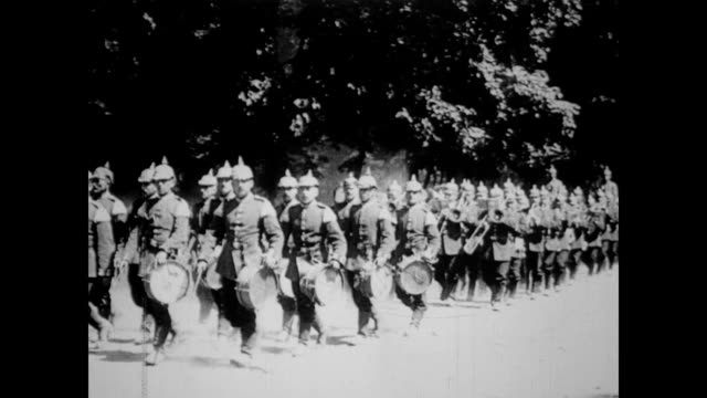 German soldiers marching along road / soldiers with drums and trumpets playing and marching through field / soldiers driving horse and loaded carts...