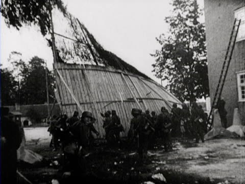 German soldiers remove a high wooden fench and a border barrier then enter the city
