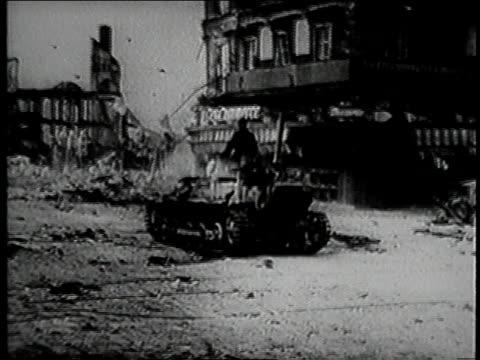 German tank driving past destroyed buildings / burning buildings