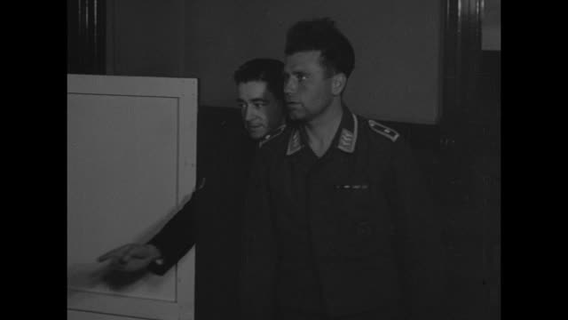 Germans escorted by British soldiers / heavy quilted flak jackets and man examines black jack boot / VS prisoner enters room takes seat at table hand...