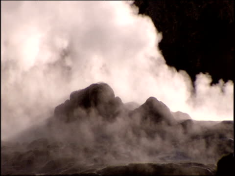 Geyser erupts spitting out stream of vapour Yellowstone National Park USA