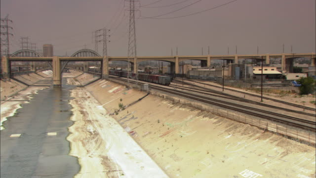 WS PAN Giant concrete riverbed of Los Angeles River with concrete bridge with large steel arches and railroad tracks along side / Los Angeles, California, USA