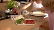 Girl and boy making vegetable pizza in kitchen