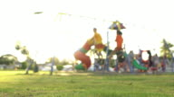 Girl and boy play Swing at playground.