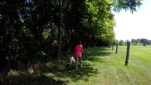 girl and dog walking away down grassy tree lined path