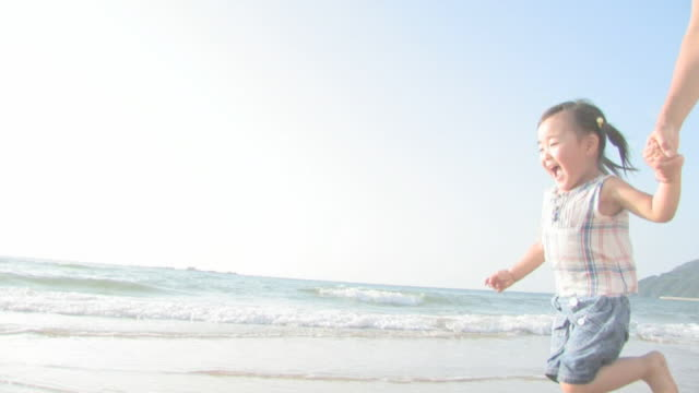 Girl and father running on beach