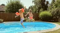 SLO MO CS A meisje en haar jongere broer springen in het zwembad