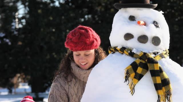 MS Girl (4-5) and mother building snowman / Richmond, Virginia, USA