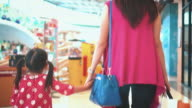 Girl and Mother Carrying Bags In Shopping Mall,Steadicam shot