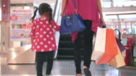 Girl and Mother Carrying Bags On Escalator In Shopping Mall